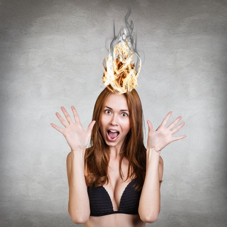 hair problem: Woman having her brain on fire because of stress on a gray background