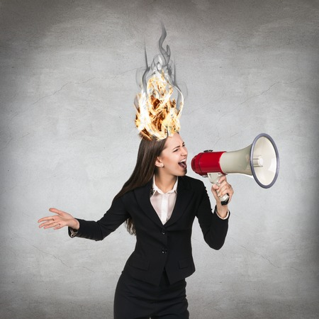 hysterics: Woman having her brain on fire because of stress on a gray background