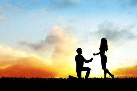 sexy bride: Silhouette couple on the sunset and man makes a proposal Stock Photo