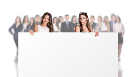 Two businesswomen holds a big placard on the blurred people background. Over white background.