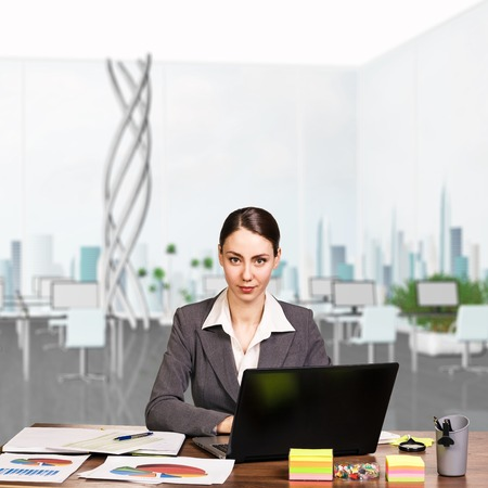woman  laptop: Attractive business woman working at the desk with sticky notes and laptop Stock Photo