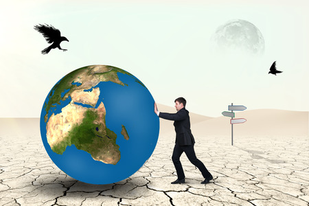 pushes: Businessman pushes world sphere in desert .Elements of this image furnished by NASA