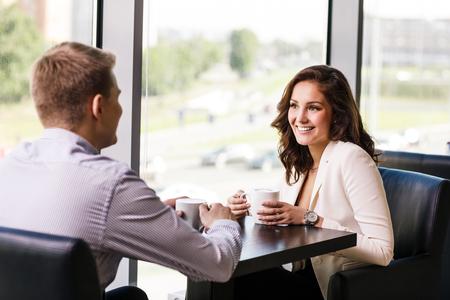Coppia godendo di caffè e parlando in caffetteria