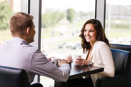 Couple enjoying coffee and talking in cafe