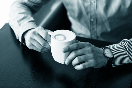 energizing: Businessman taking a break at the office as he enjoys a cup of hot aromatic coffee, close up view of his hands