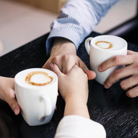 drinking coffe: Las manos en la mesa la celebraci�n de tazas de caf� Foto de archivo