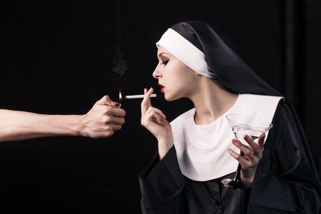 black nun: Smoking young nun. Studio shoot on black backround