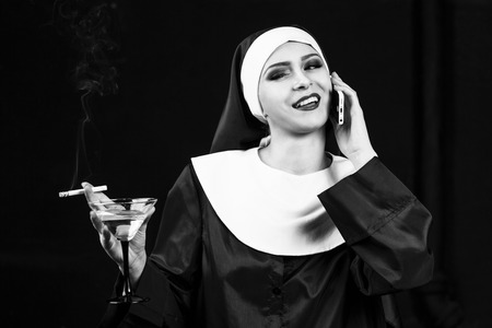 sinner: Smoking young nun. Studio shoot on black backround