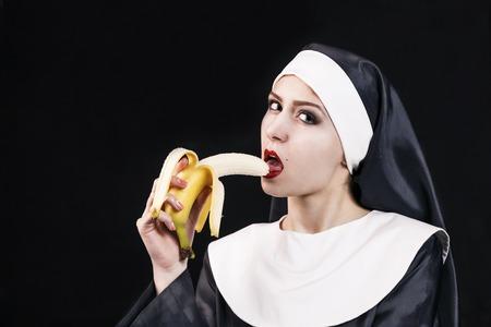 nun: Young nun in religious concept eat banana Stock Photo