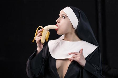black nun: Young nun in religious concept eat banana Stock Photo