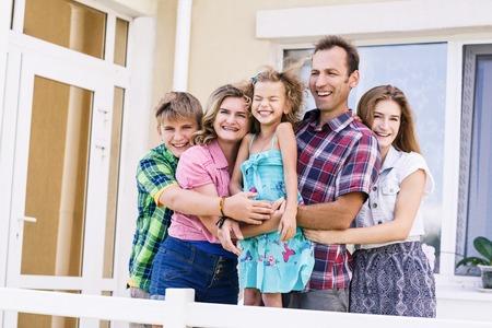 Grote gelukkige familie staat naast hun huis Stockfoto