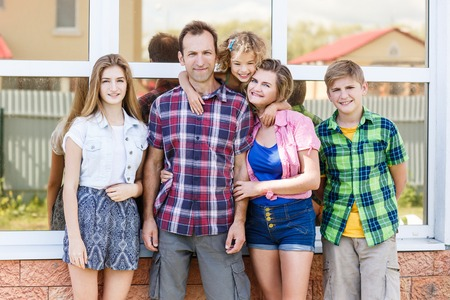 head home: Big happy family stands beside their house