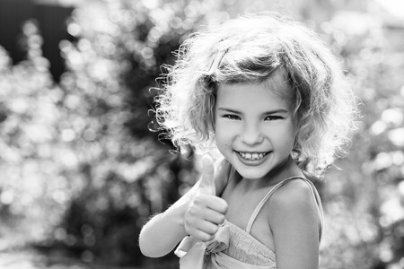 cute blonde: Cute little girl smiling in the park in summer day