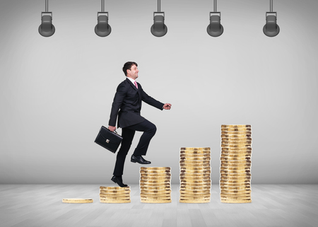 upstairs: Business concept - business man go upstairs with grey wall background. Stairs from coins. Stock Photo