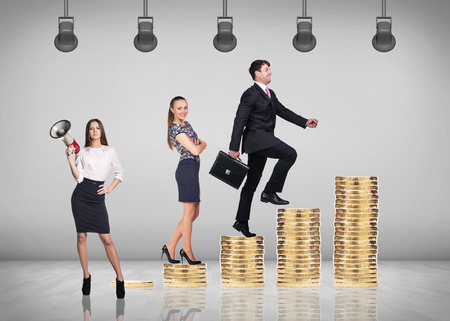 winning stock: Business concept - businessman and woman go upstairs with grey wall background. Stairs from coins. Stock Photo