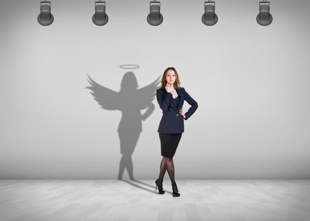 spotlight on wall: Businesswoman stands in the middle of the room with shadow on the wall Stock Photo