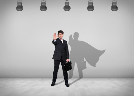 Businessman stands in the middle of the room with shadow on the wall