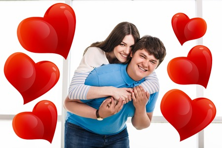 carrying girlfriend: Man carrying girlfriend on his back with big love Stock Photo