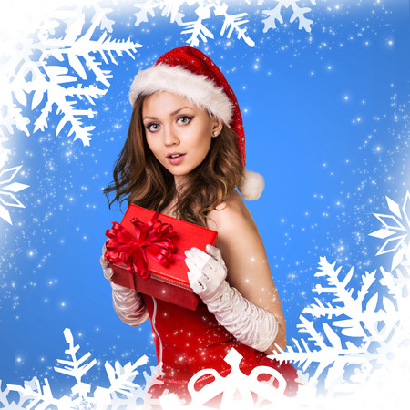 Sexy santa girl holds gift box on the snowflakes pattern Stock Photo