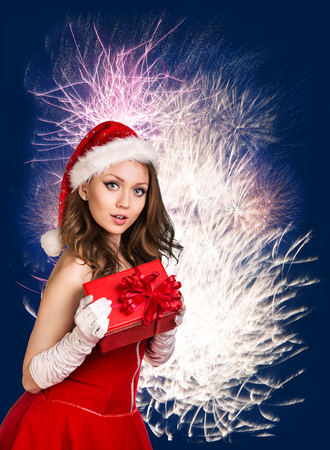 sexy girl: Sexy happy santa woman with gift box over fireworks background