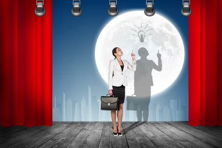stage props: Businesswoman stands on the scene with curtains over night city background