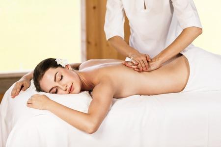 masaje: Muchacha hermosa joven que yace en mesa de masaje y disfrutar de masajes. Foto de archivo