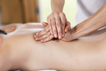 natural therapy: Beautiful young woman getting back massage at spa Stock Photo