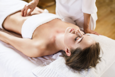 massagist: Beautiful brunette woman enjoys massage of tummy at the health spa Stock Photo