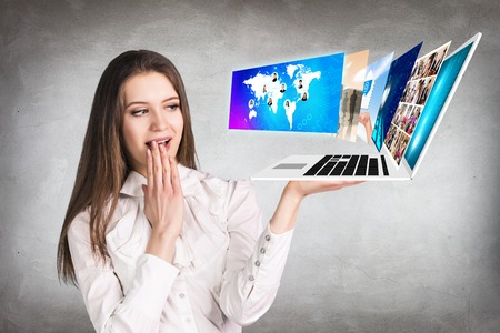 computer screens: Happy young woman showing a laptop with many screens on the open hand palm on the gray background.