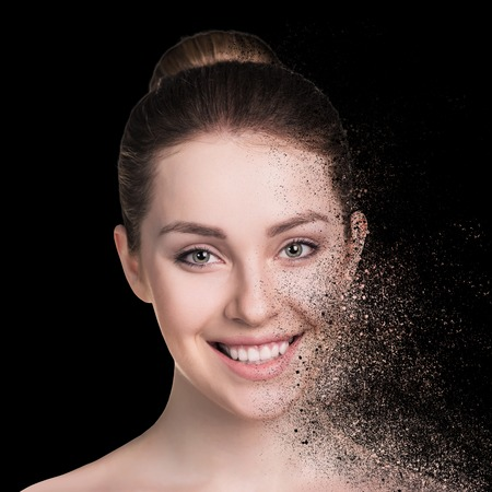 dispersion: Beautiful woman face isolated on black background.