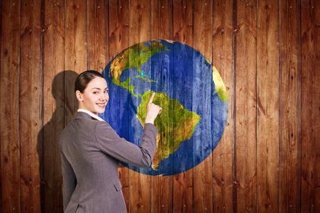 bola del mundo: La mujer se coloca cerca de la Tierra bola de textura en el fondo de madera. Foto de archivo