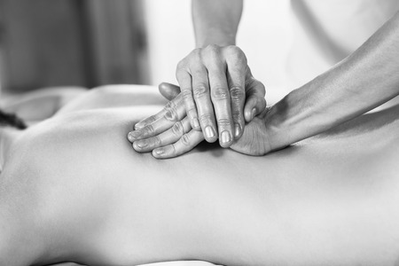 in the back: Beautiful young woman getting back massage at spa Stock Photo