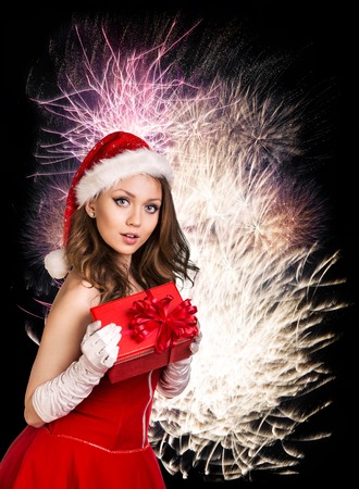 woman face close up: Sexy happy santa woman with gift box over fireworks background