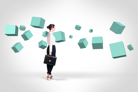 full suspended: Business woman looking at turquoise cubes suspended in the air. Abstract isolated on white.