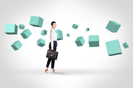 full suspended: Business woman stands near turquoise cubes suspended in the air. Abstract isolated on white. Stock Photo