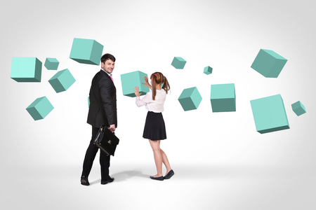 full suspended: Businessman and woman stand near turquoise cubes suspended in the air. Abstract isolated on white. Stock Photo
