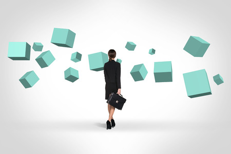 Business woman looking at turquoise cubes suspended in the air. Abstract isolated on white.