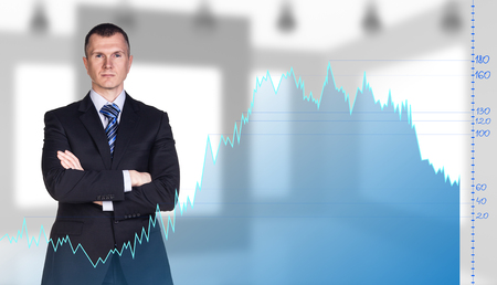 financial data: Businessman stands behind the big graph on the office background.
