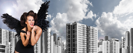 angry angel: Young dark angel woman stands on the urban background.