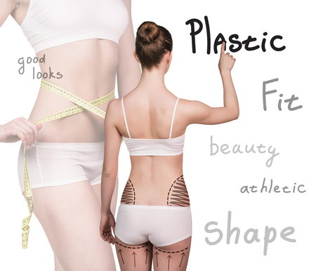 Women Cellulite: Young woman stands back and makes a notes on the wall. Isolated plastic boby.