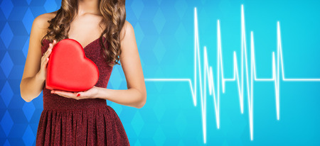 physical exam: Young woman present heartbox beside pulse line on the blue background
