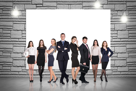 Group of business people stands on the brick wall background Stock Photo