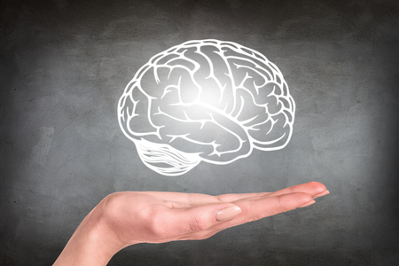 Drawn brain hovered over the human hand on the gray wall background