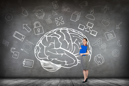 mental object: Woman stands beside big drawn brain on the gray wall