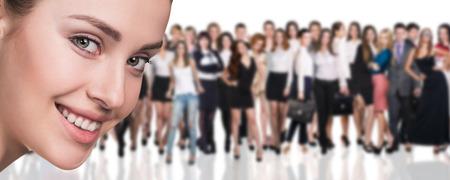 Grande folla di uomini d'affari e giovane donna in primo piano. Isolato su sfondo bianco