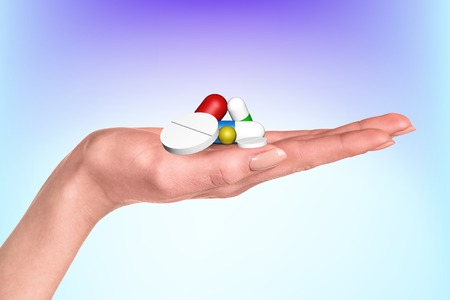 antidepressants: Drug capsules and pills in hand on the blue background