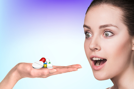 antidepressants: Young woman and drug capsules and pills in hand on the blue background Stock Photo