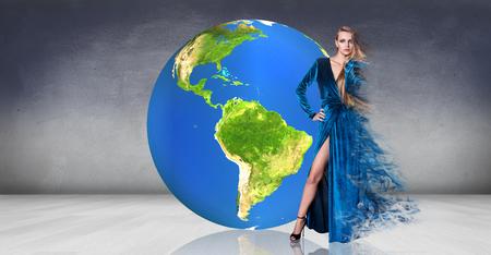 world of work: Model  posing near big earth ball in the gray room