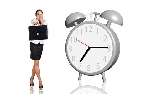 stretch out: Business women stand near big gray alarm clock isolated on the white