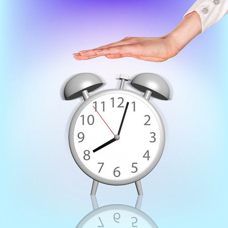 past midnight: Alarm clock stands on the blue background and womans hand atop